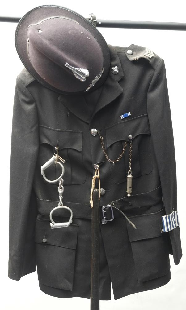 A 20th century police tunic with Northumbria Police helmet: together with handcuffs,