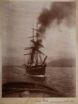 A mounted photograph of RYS Terra Nova under tow inscribed to border 'SY Terra Nova arrival from