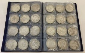 A folder containing 72 assorted white metal coins from around the world.