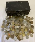 A black metal cash tin containing vintage British and foreign coins.