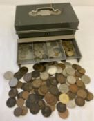 A green metal cash tin containing a collection of antique and vintage coins.