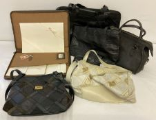A collection of vintage leather and faux leather bags and leather zipped case writing set.