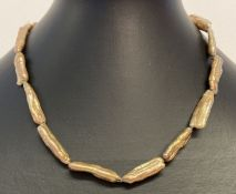 A bronze baroque stick pearl necklace with silver lobster style clasp and extension chain.