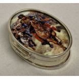 A small oval shaped pill box with ceramic plaque set to lid depicting charging cavalrymen.