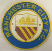 A circular shaped painted cast iron Manchester City F.C. wall plaque.