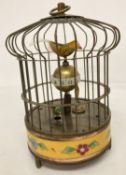 An ornamental wind up birdcage clock with yellow cloisonné panel to base.
