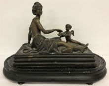 A filled bronze figure of a reclining semi naked classical female with cherub offering fruit.