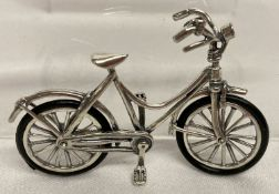 A small 925 silver bicycle with rubber tyres and movable handle bars and front wheel.