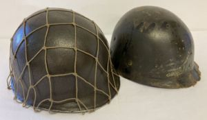 A WWII style US M1 helmet with Capac liner and string cam net.
