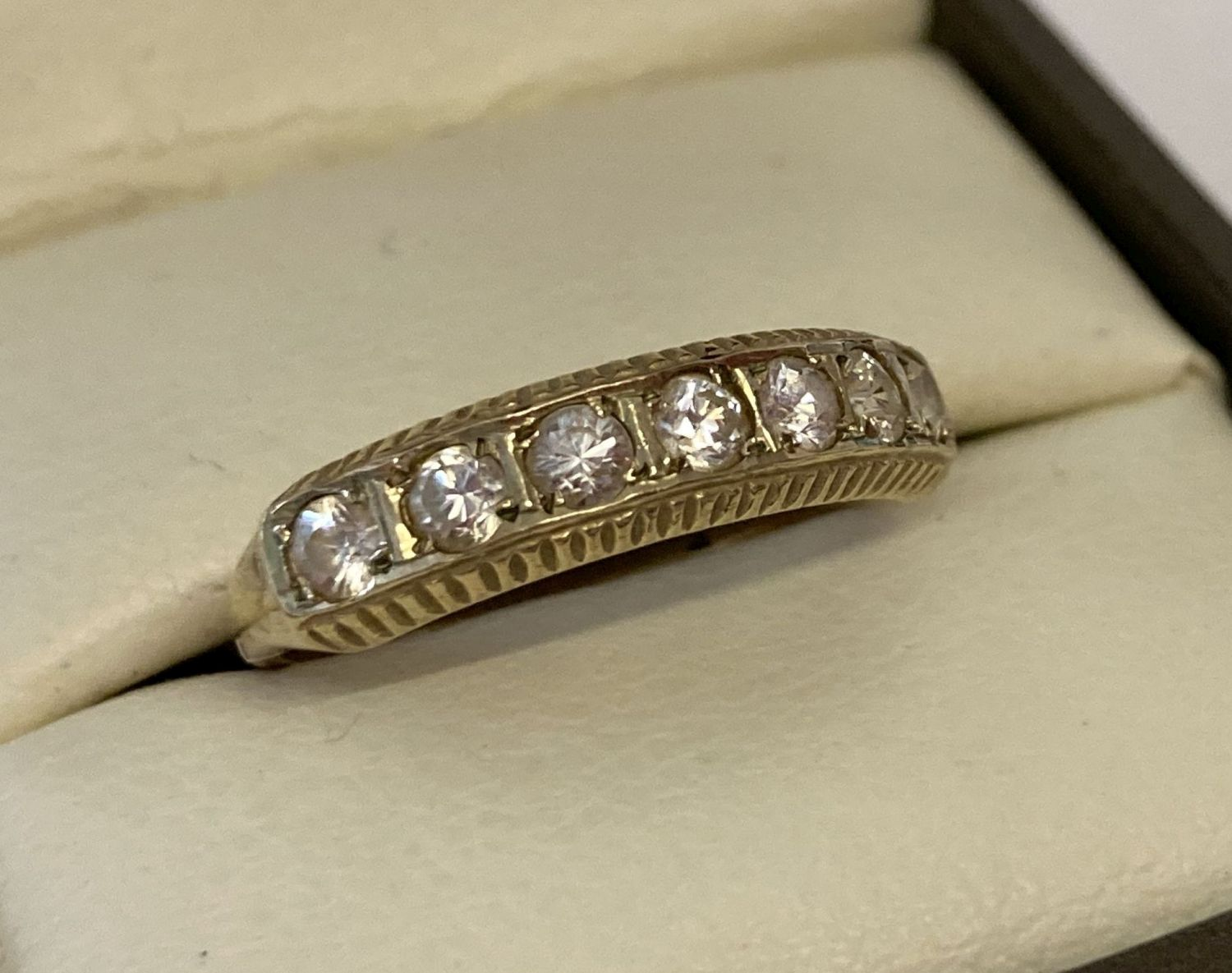 A vintage gold half eternity ring set with 7 clear stones.