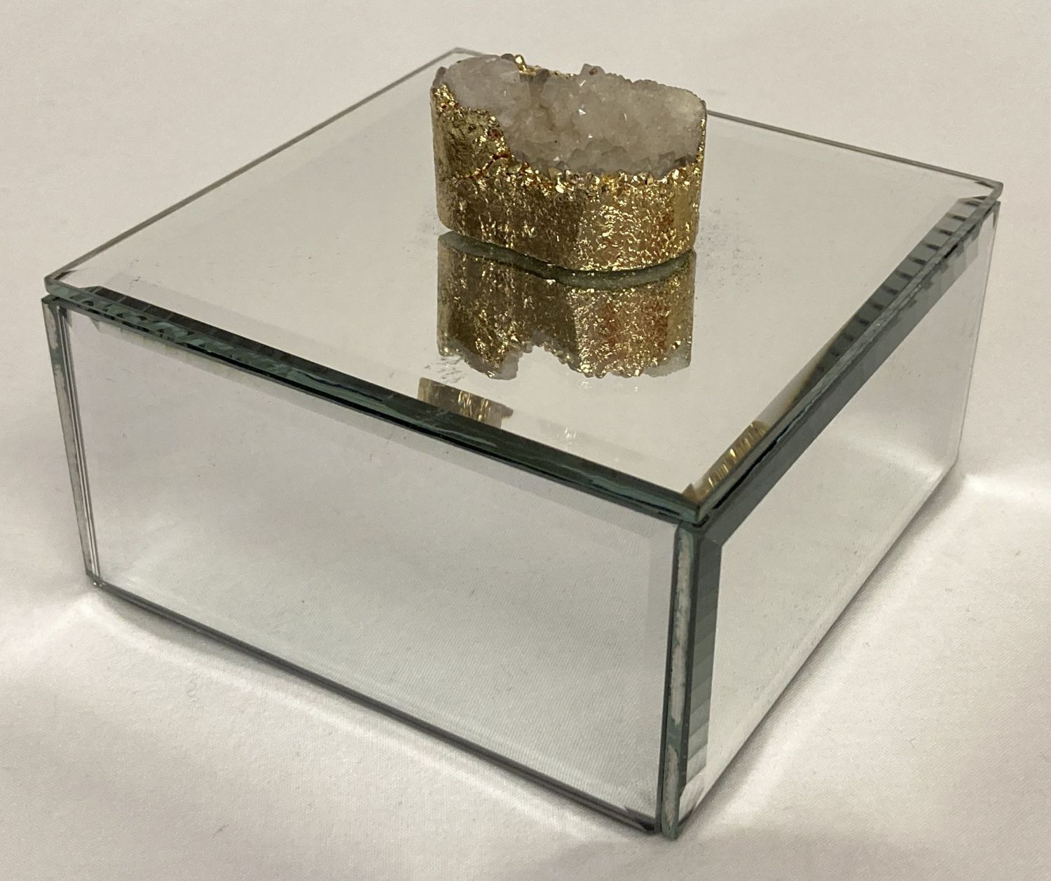 A modern mirrored jewellery box with druzy stone set as lid handle.