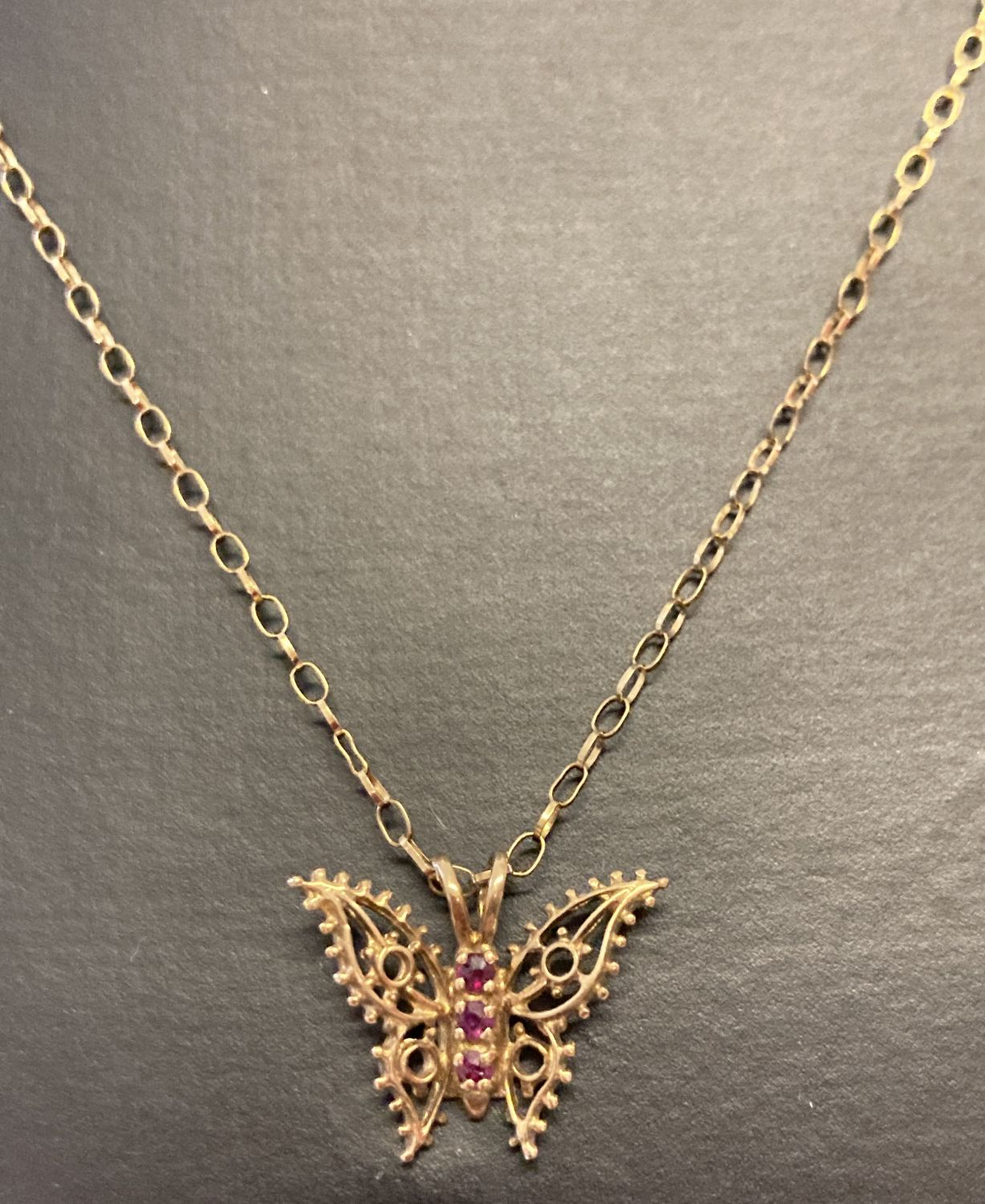 A gold open work butterfly pendant set with 3 small rubies, on an 18 inch belcher chain.