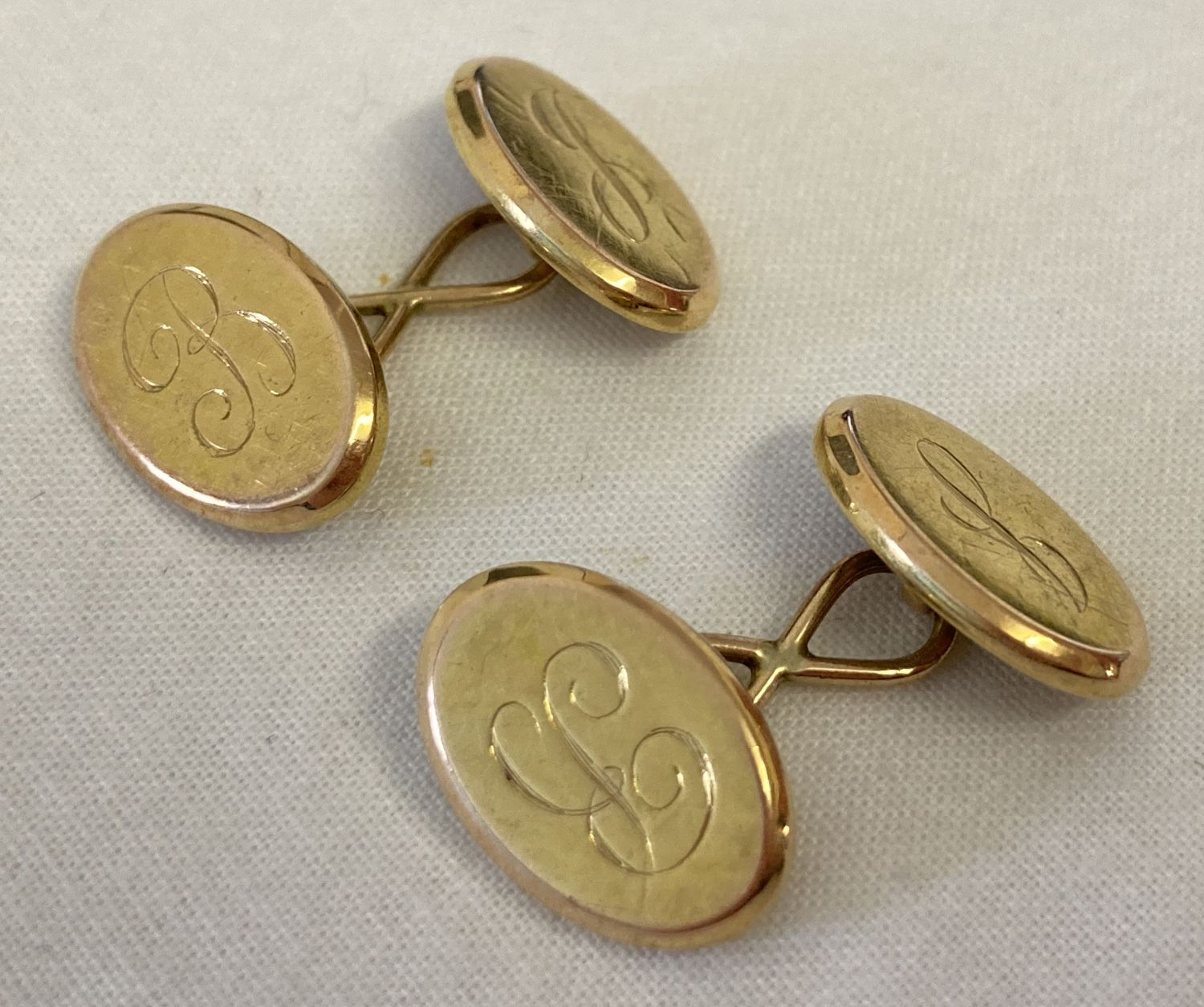 A pair of gold oval shaped cufflinks with engraved initials J & B.