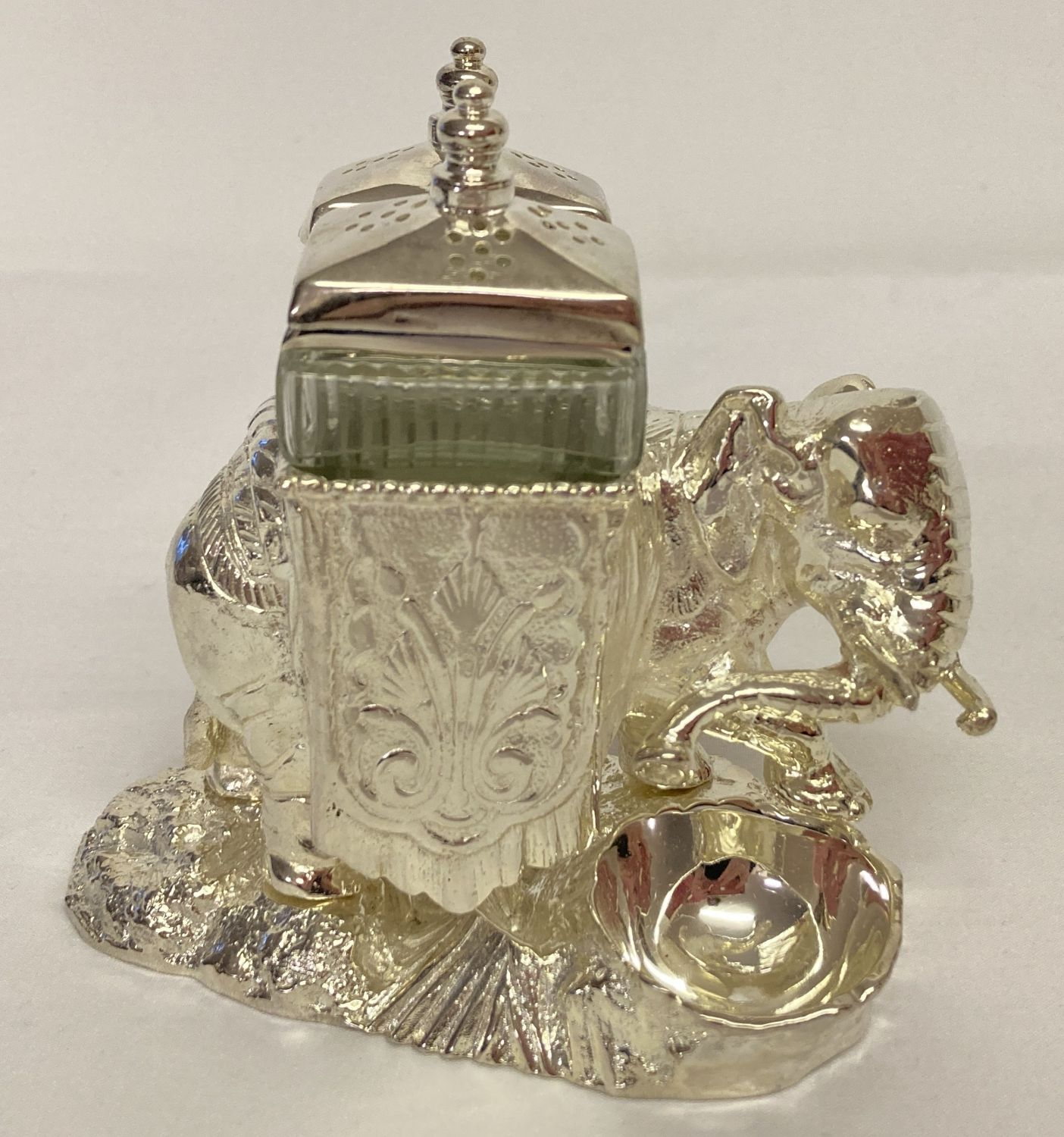 A modern silver plated cruet in the shape of an elephant, with cut glass bottles & engraved detail.