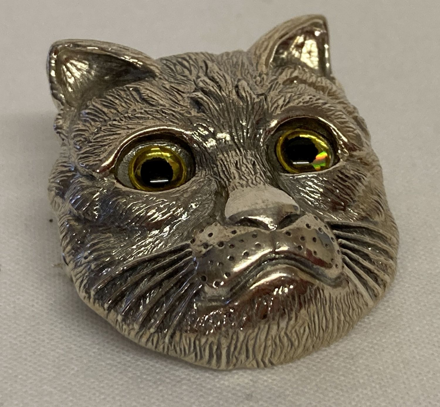 A silver pendant brooch in the shape of a cats head with glass set eyes.
