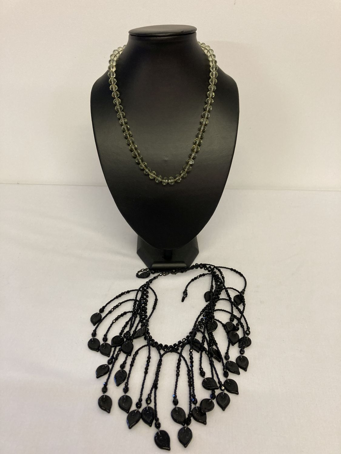 2 glass bead necklaces. A modern design black glass drop style statement necklace with leaf detail.