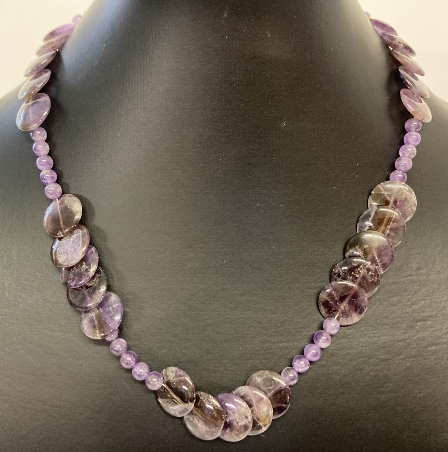 """A 17"""" amethyst beaded necklace with circular and spherical shaped beads & a white metal T bar clasp."""