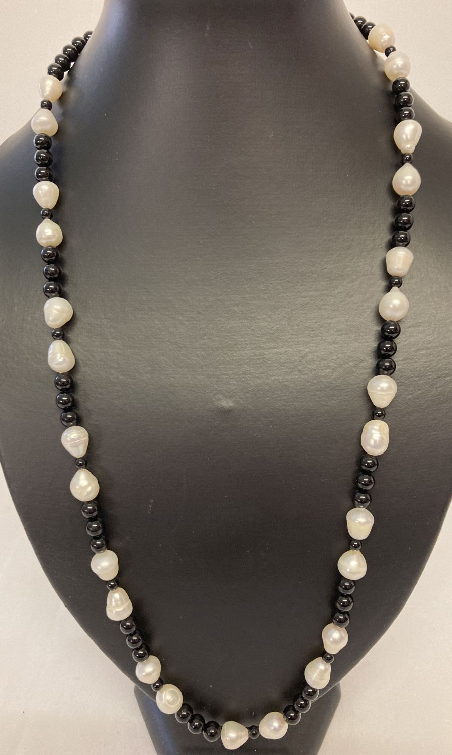 """A 25"""" large freshwater pearl and onyx beaded necklace with silver tone S shaped hook clasp."""