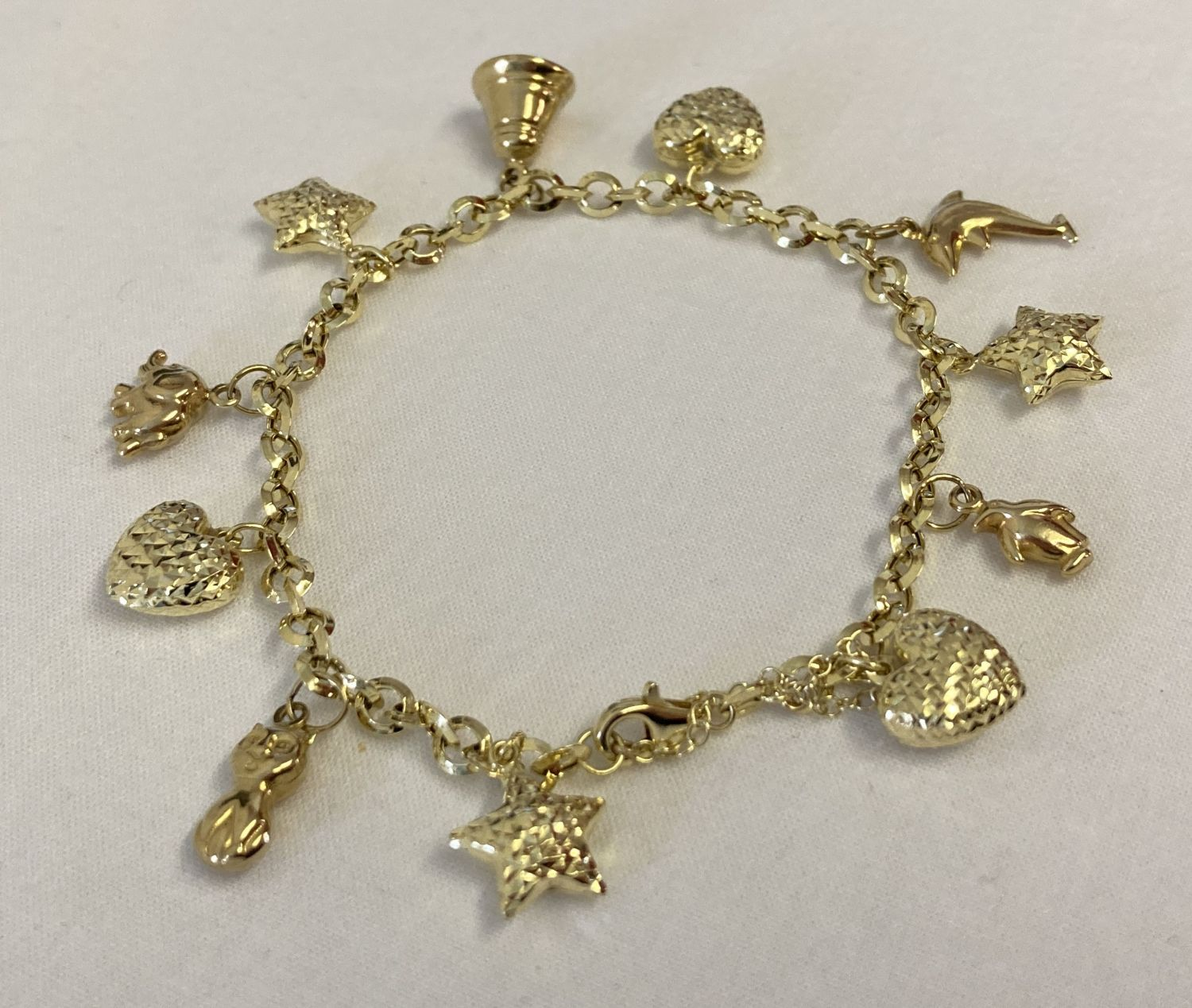 A modern 9ct gold charm bracelet with fixed charms and safety chain.