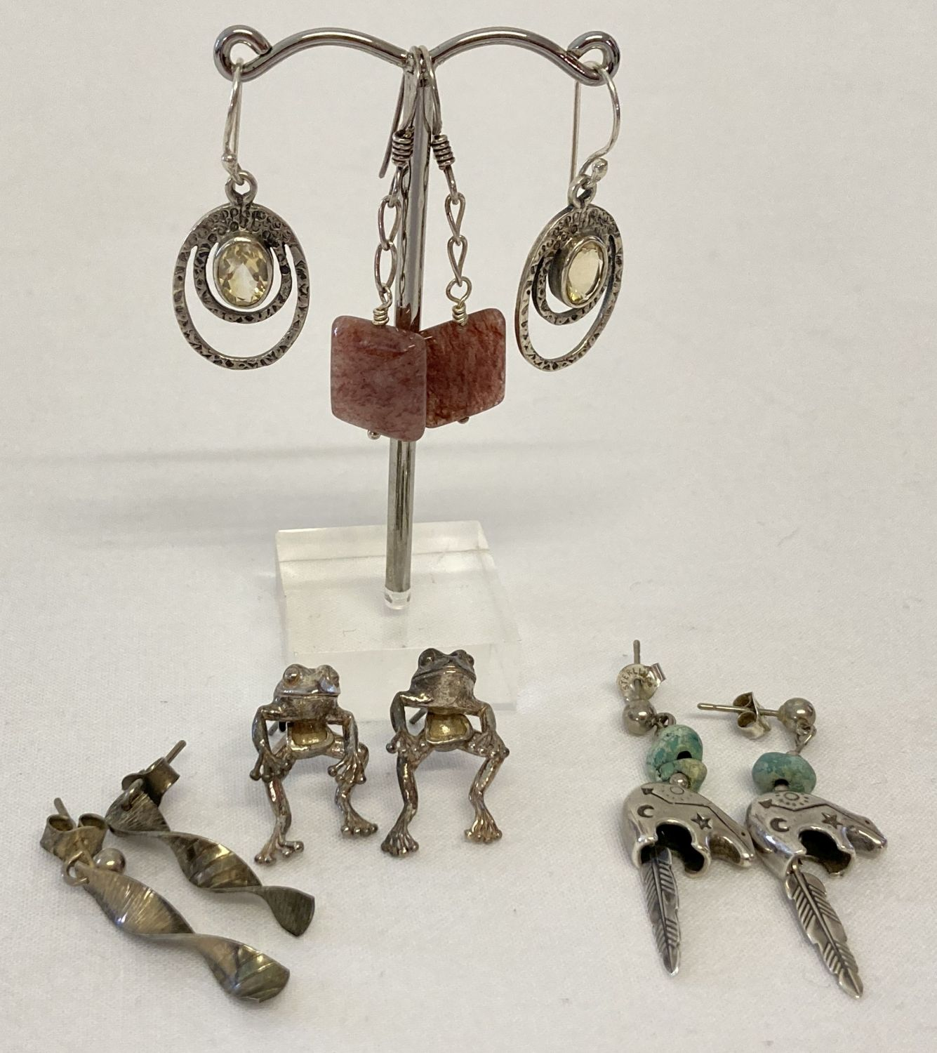 5 pairs of silver and white metal earrings, all in a drop style. To include stone set and frogs.