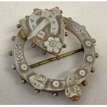A vintage silver circular shaped sweetheart brooch with shield, horseshoe and dagger detail.