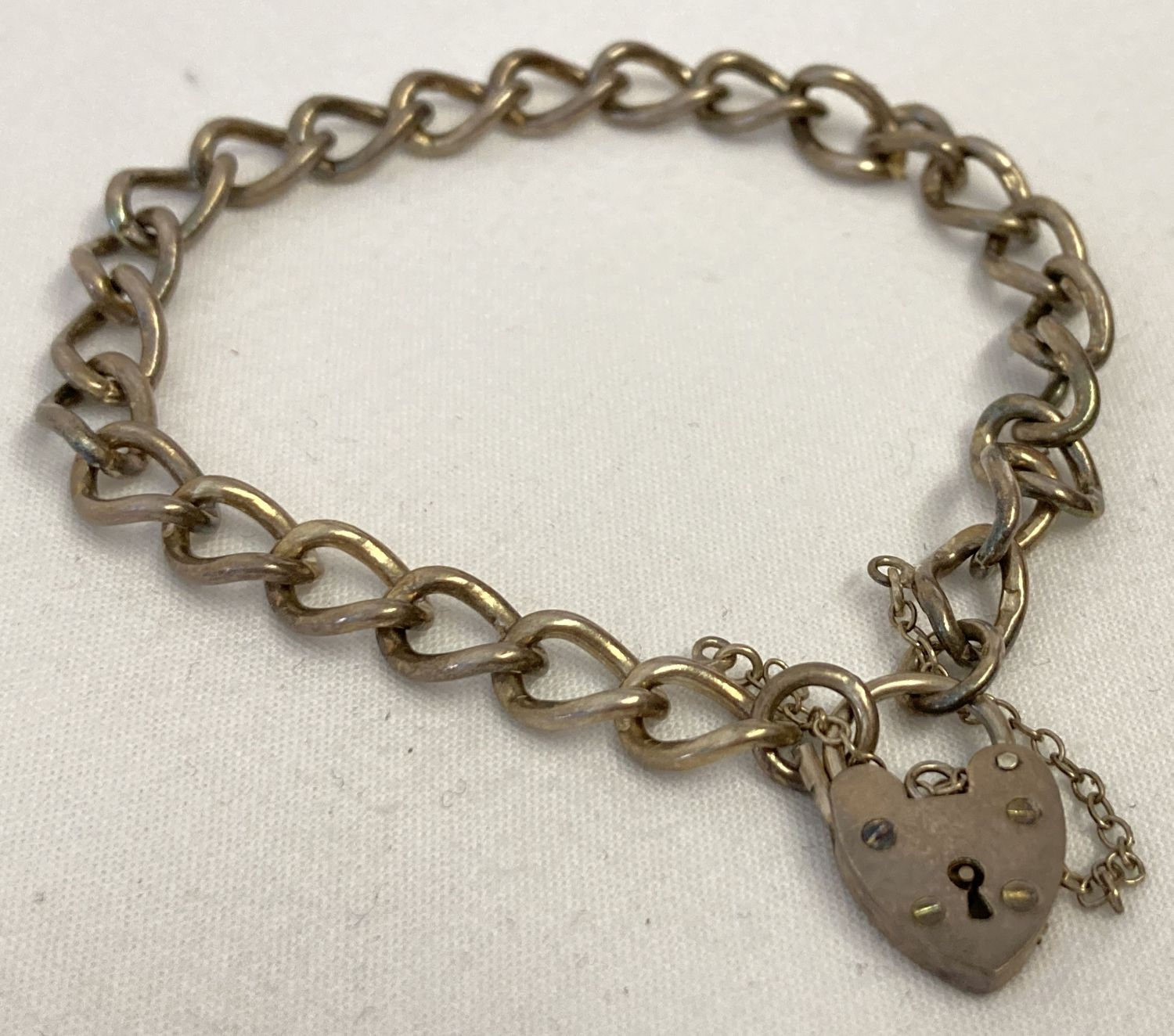A vintage curb chain charm bracelet with padlock and safety chain.