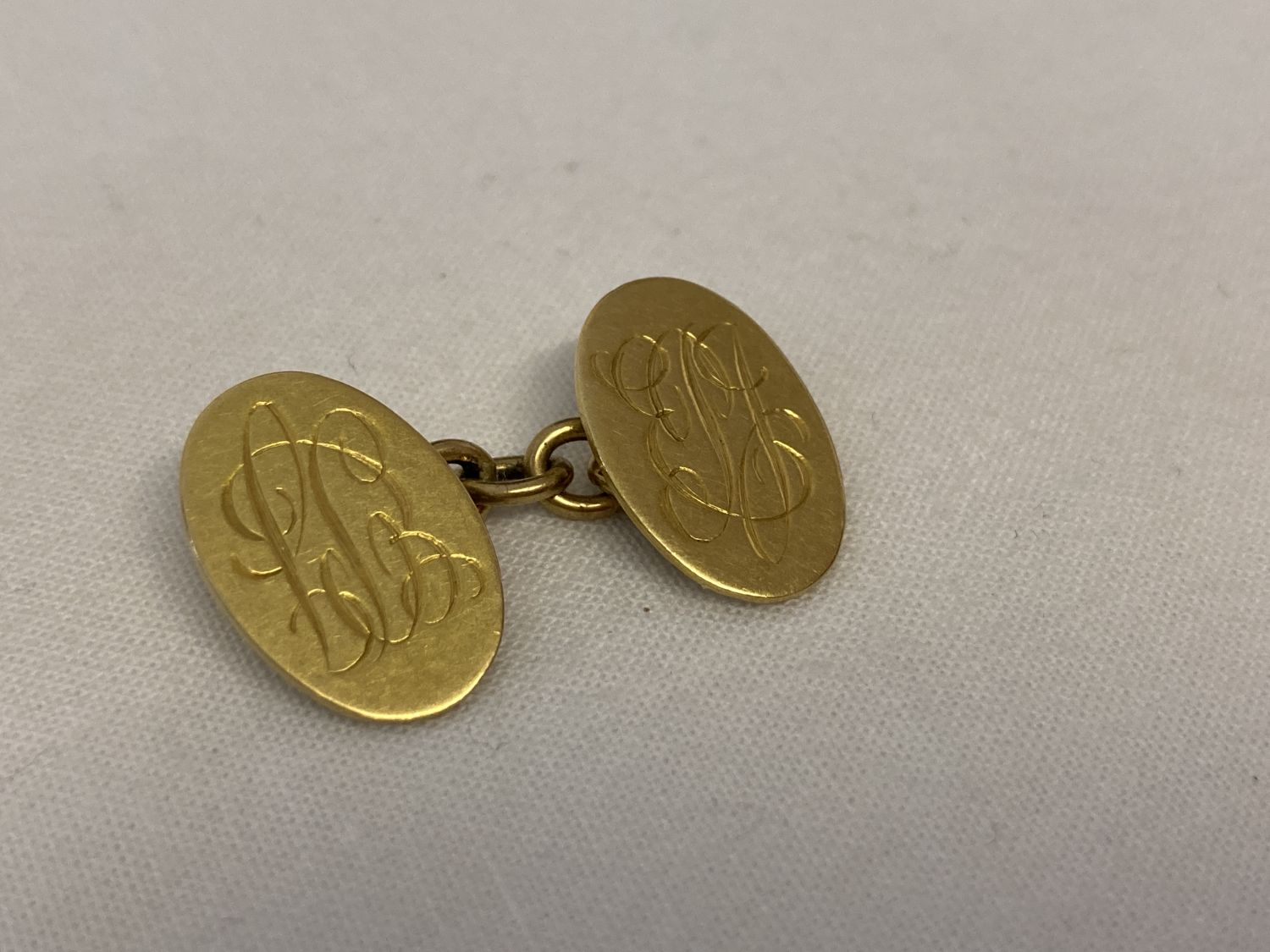 A scrap gold single 18ct gold cufflink with engraved monogram initials.