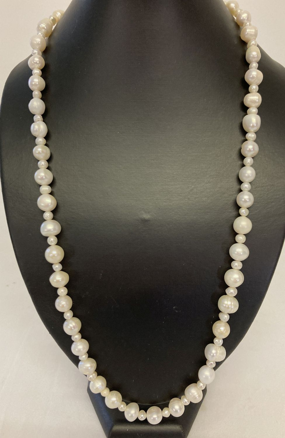 """A 26"""" beaded necklace made from alternating large and small freshwater pearls."""