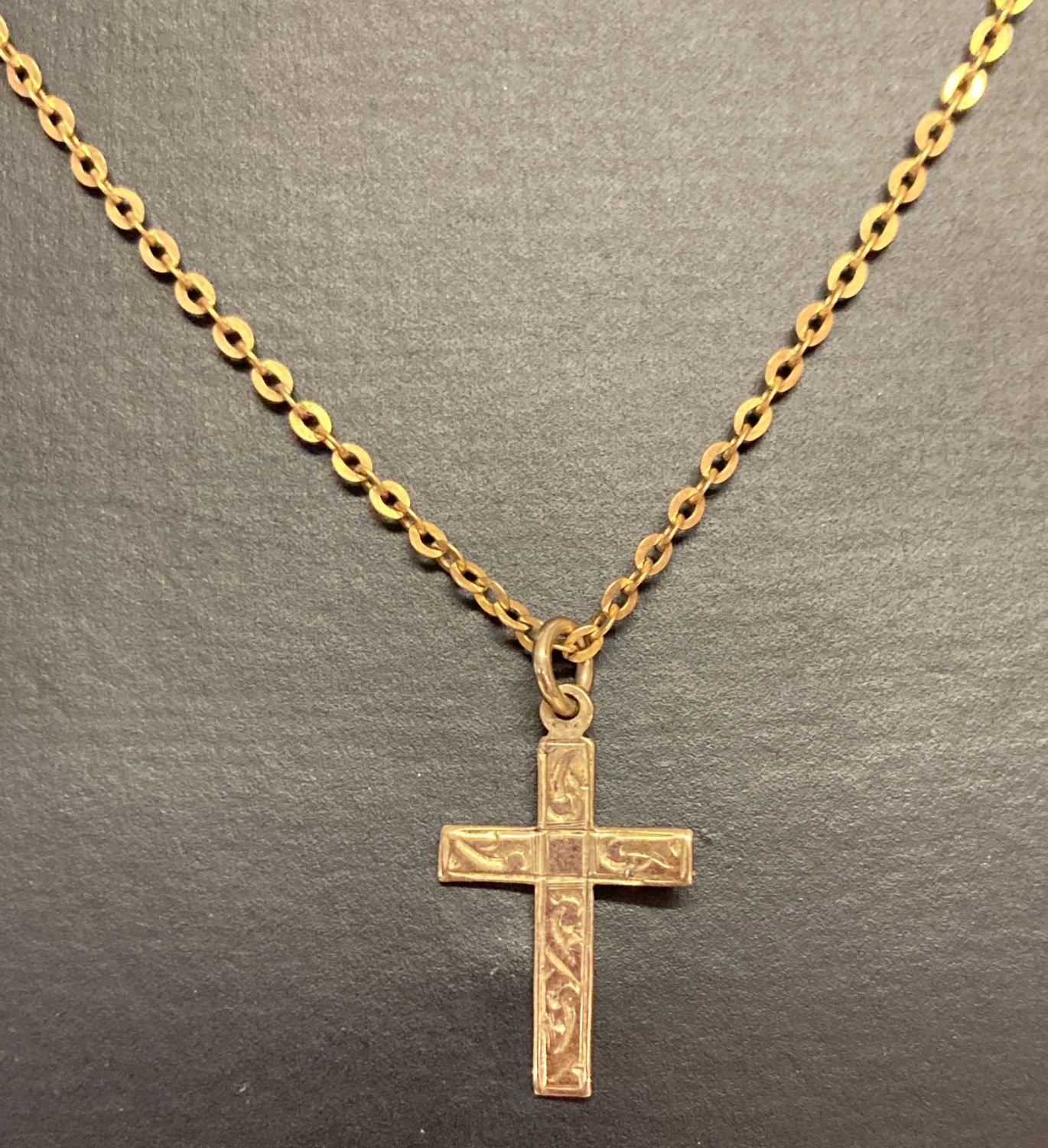 """9ct gold cross pendant with engraved detail on a 16"""" 9ct gold chain."""