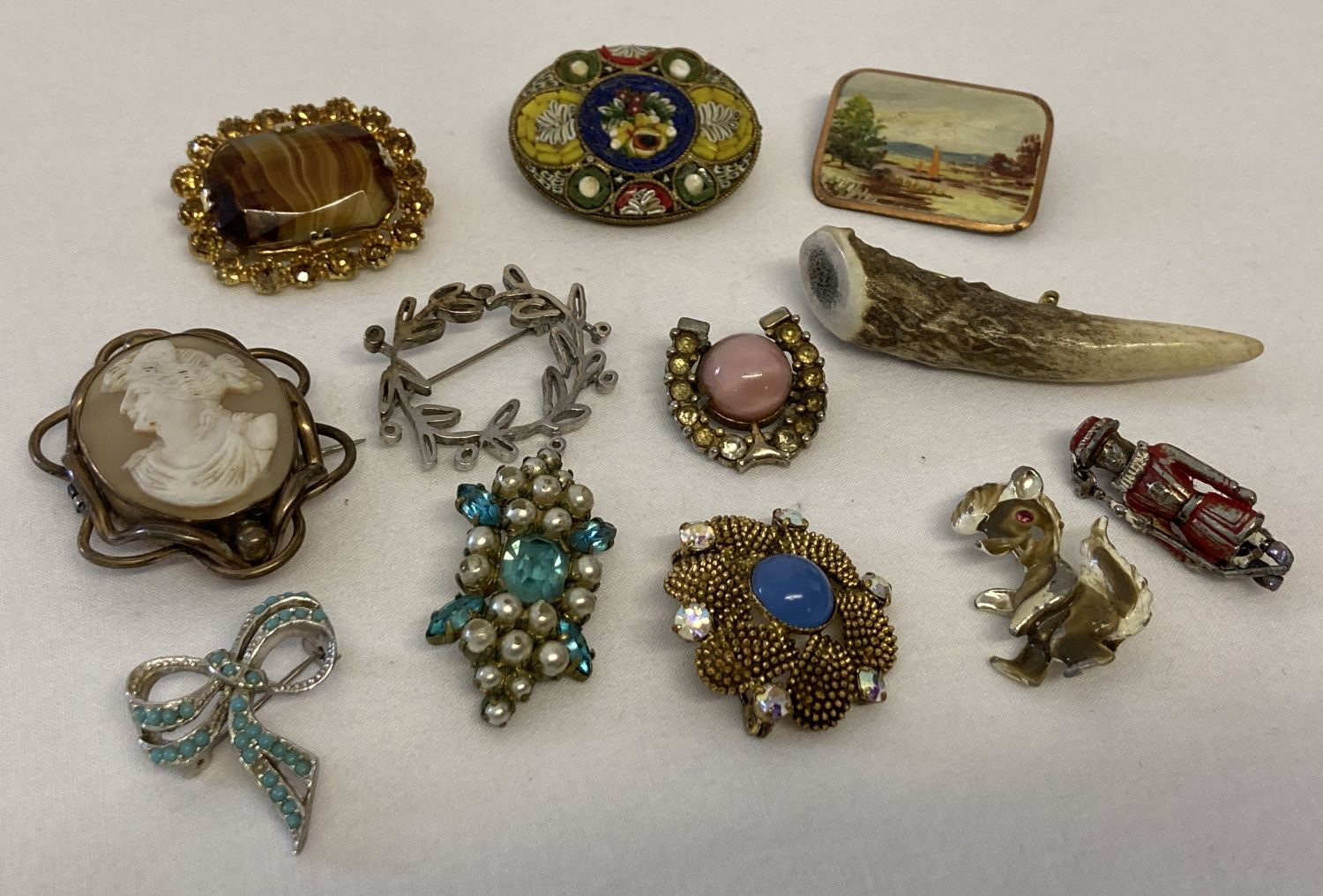 12 vintage brooches to include silver and stone set. Examples from Sphinx and Hollywood.