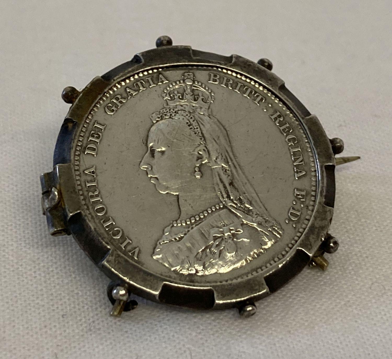 An 1887 Victorian Jubilee head silver shilling, set in a vintage brooch mount.