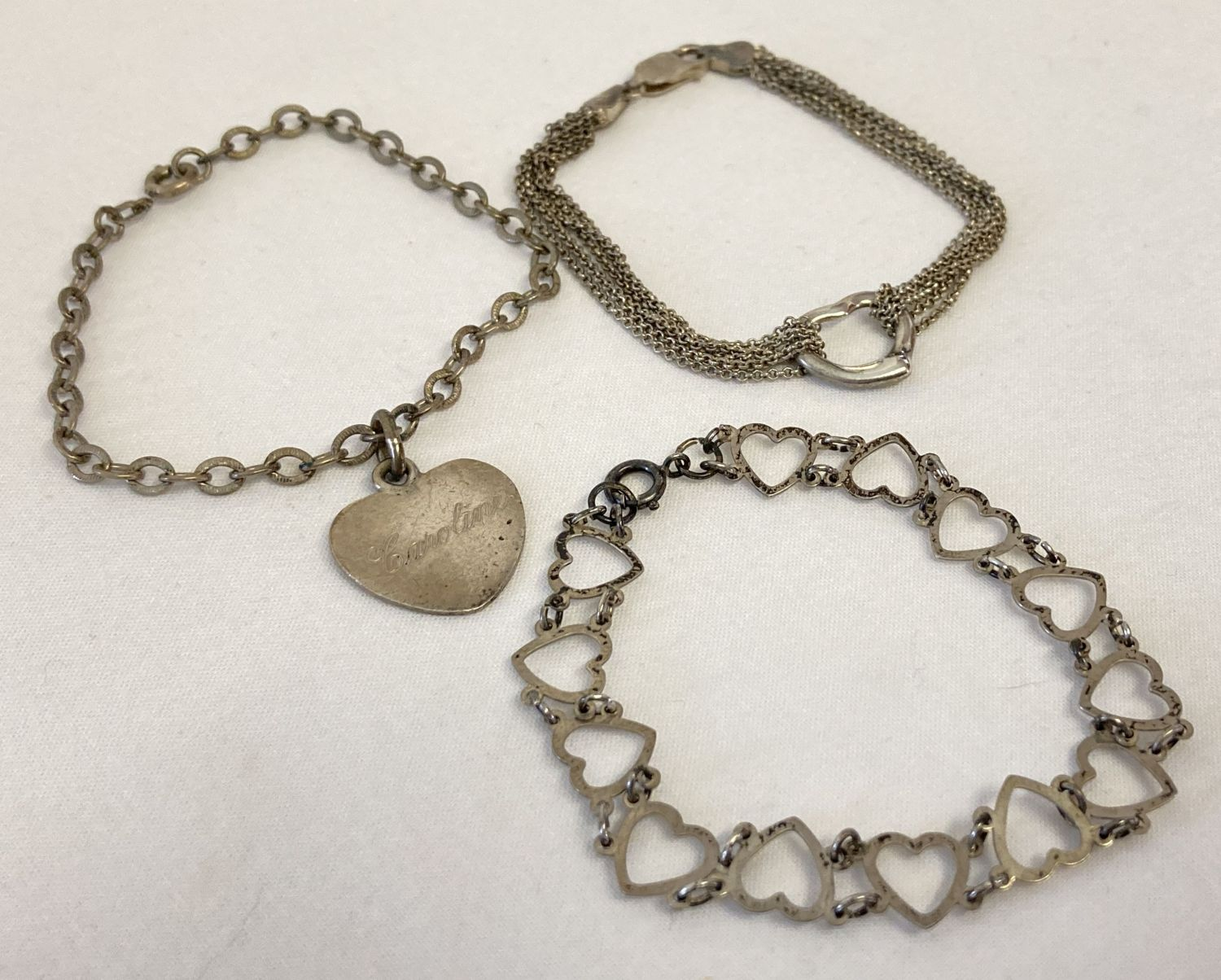 3 silver bracelets. Heart link bracelet, belcher chain with heart shaped charm and a multi chain