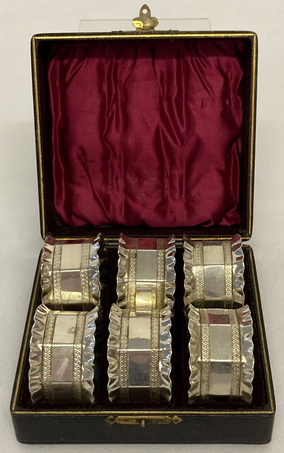 A boxed set of vintage silver plated, decorative napkin rings with engraved borders & frilled rims.