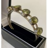 A modern bangle style silver plated bracelet set with 5 large oval cut green stones.
