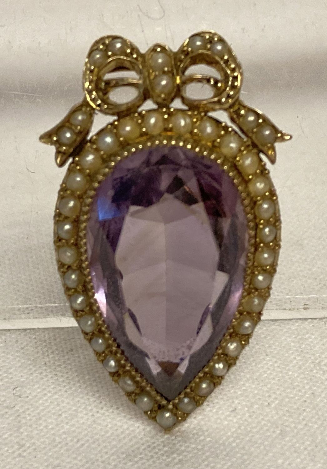 A Victorian pendant brooch, tests as 14ct gold, set with central teardrop shaped amethyst.