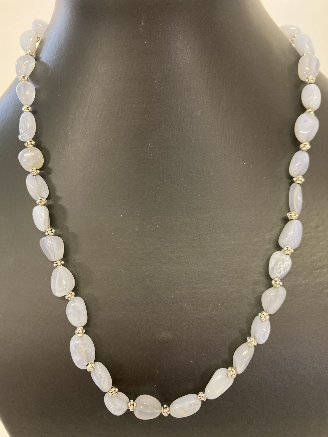 """A 20"""" blue chalcedony and white metal beaded necklace with decorative silver tone T bar clasp."""