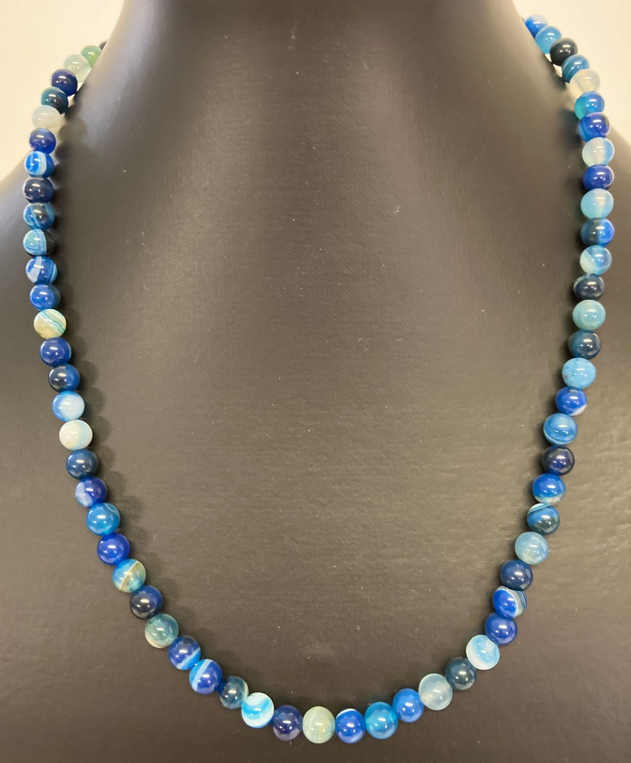 "An 18"" costume jewellery necklace made from polished blue banded and dyed agate beads."