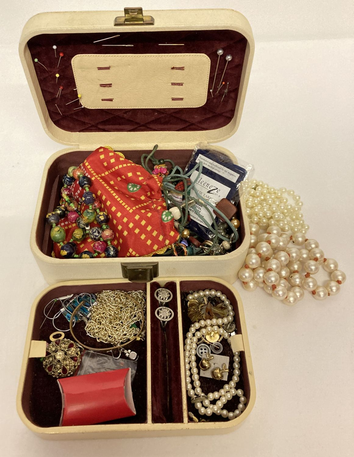 A vintage cream coloured jewellery box and contents.
