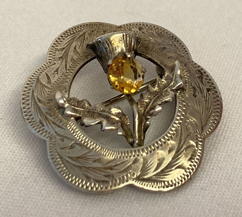 A vintage Scottish silver brooch with citrine set thistle design.
