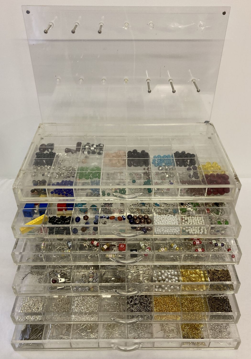 A jewellery makers Perspex chest of drawers and hanging hooks back panel.