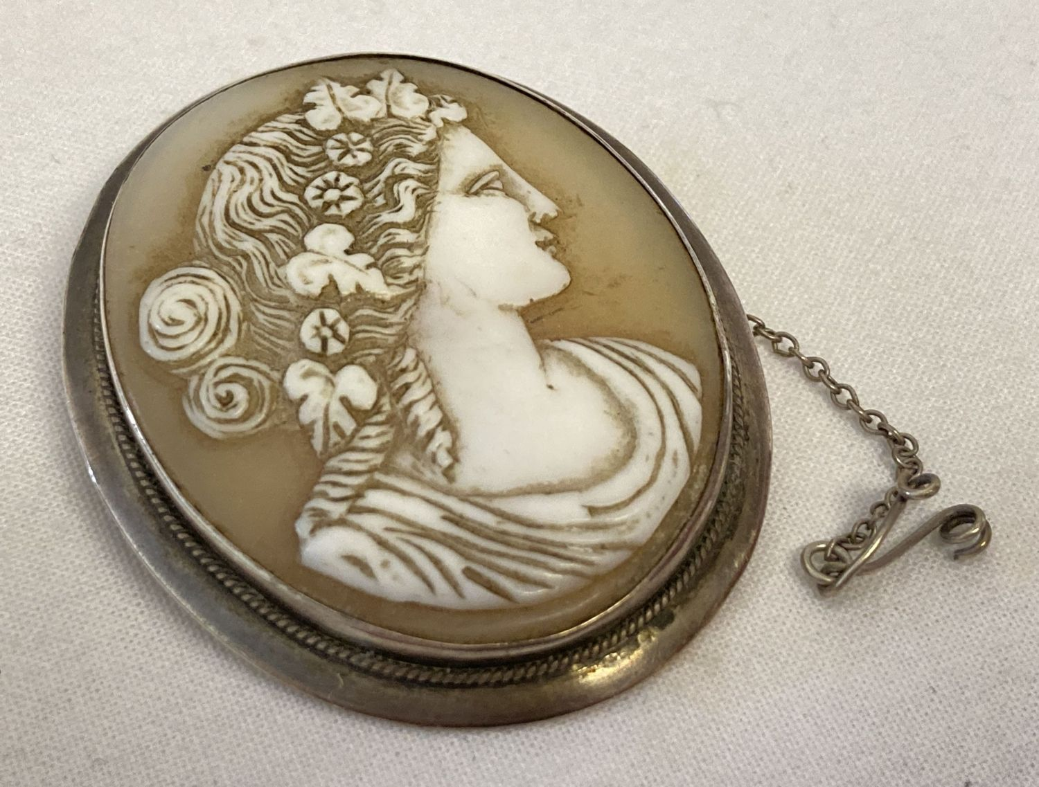 A large vintage white metal cameo brooch with safety chain, pin missing.