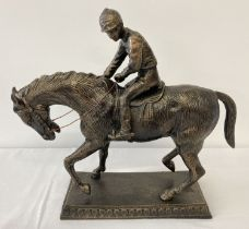A large bronzed cast metal figurine of a horse and jockey.