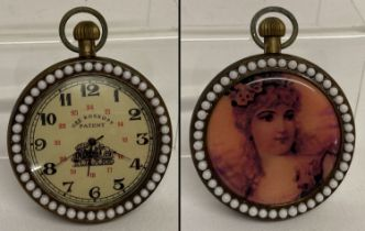 A brass cased top winding pocket watch with beaded detail to surround front and back.