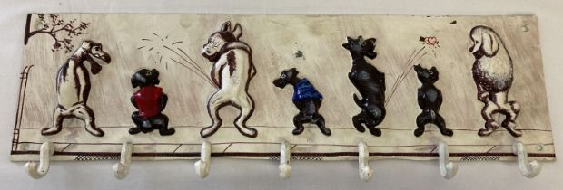 A wall hanging coat/cup hook with dog detail.