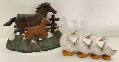 2 decorative painted cast metal doorstops in the shapes of horse and foal and row of ducks.