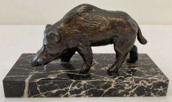 A small bronze boar figure on a black and white marble base.