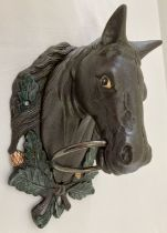 A large painted cast metal, wall mountable horse head with ring.