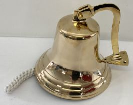 A large brass wall mountable bell with rope handle.