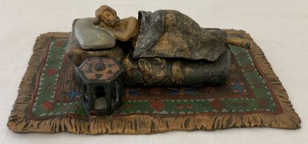 After Bergmann - a cold painted figurine of a sleeping woman on a floral carpet. Marks to base.