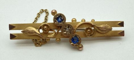 An Edwardian 9ct gold floral design bar brooch set with a small round cut diamond and 2 small